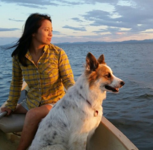 Amelia sits on a boat in the open water. She and her white and brown dog look out towards the setting sun.